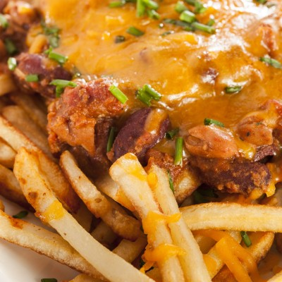 20972528 - unhealthy messy chili cheese fries on a background