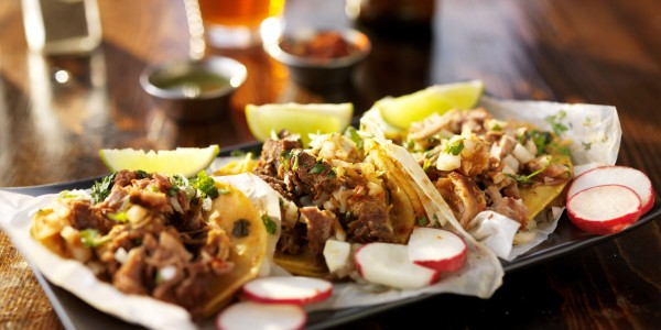 47617649 - three tacos with beer on wooden table top served with limes and radishes